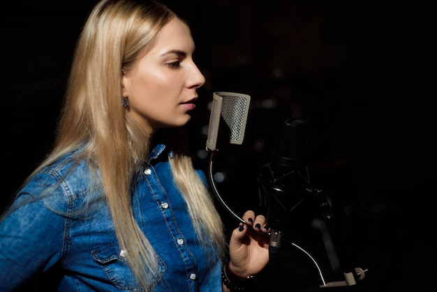 Blonde singende frau in einem tonstudio
