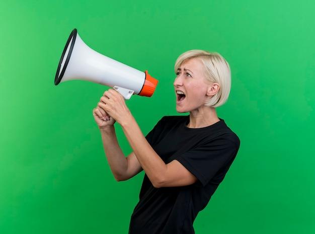 Blonde slawische frau mittleren alters, die in der profilansicht steht und in lautsprecher schreit, der gerade lokal auf grünem hintergrund mit kopienraum schaut