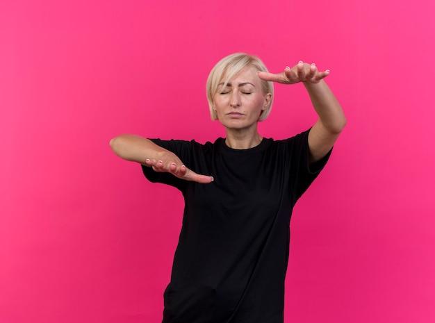 Blonde slawische frau mittleren alters, die mit geschlossenen augen geht, die hände in richtung kamera strecken, lokalisiert auf purpurrotem hintergrund mit kopienraum
