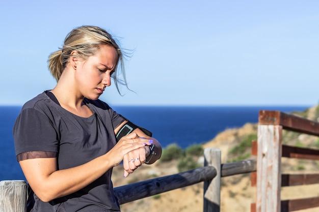 Blonde sportlerin, die smartwatch betrachtet