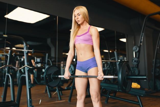 Blonde sportlerin in den minikurzschlüssen, die barbell am turnhallentraining anheben