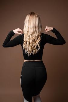 Blonde sportliche frau mit schlankem, gebräuntem körper in schwarzer sportkleidung, die auf beigem hintergrund posiert. rückansicht