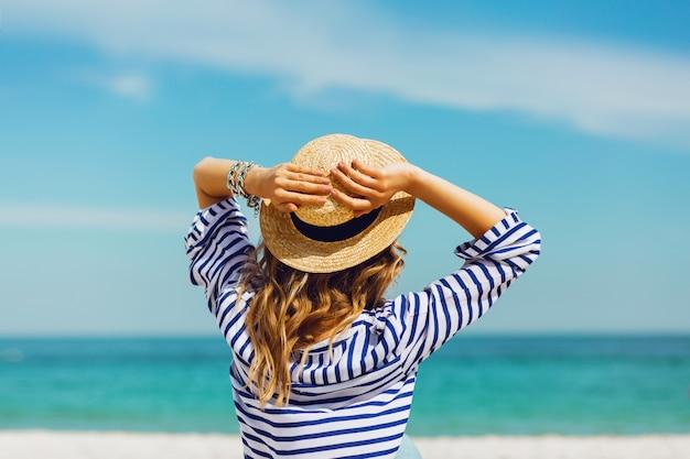 Blonde stilvolle frau im strohhut und in der sonnenbrille, die auf dem tropischen strand des paradieses aufwirft