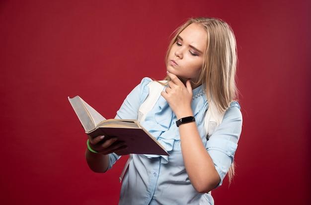Blonde studentenfrau liest ein buch und denkt sorgfältig.