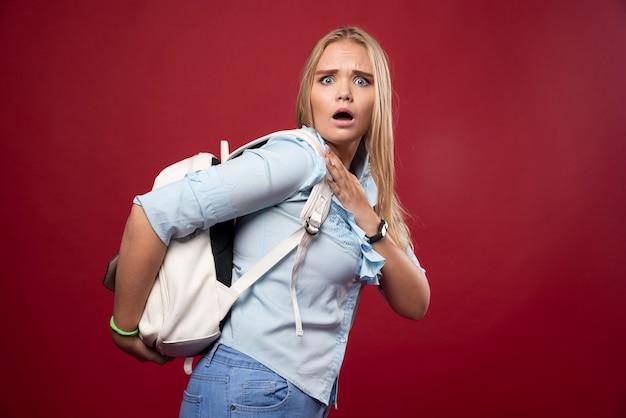 Blonde studentin, die einen schweren rucksack trägt.
