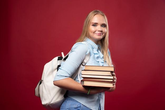 Blonde studentin, die einen stapel bücher hält und positiv aussieht.