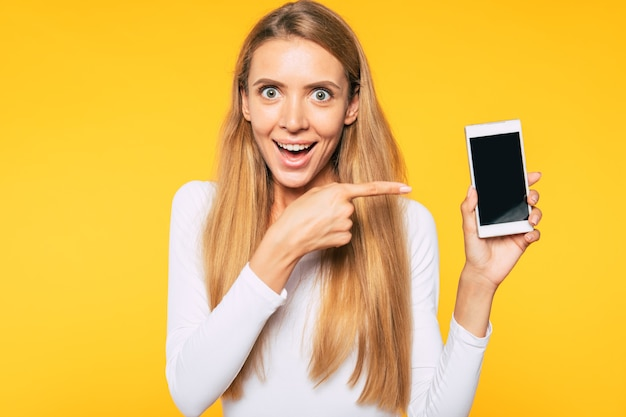 Blonde süße und schöne junge frau benutzt ihr smartphone. chatten mit freund