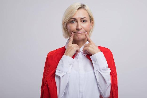 Blonde superheldin mittleren alters im roten umhang, die ein falsches lächeln macht
