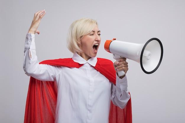 Blonde superheldin mittleren alters im roten umhang schreit im lautsprecher und schaut auf die seite, die die hand hebt