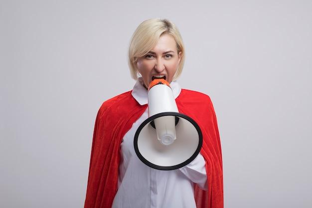 Blonde superheldin mittleren alters im roten umhang schreit im lautsprecher