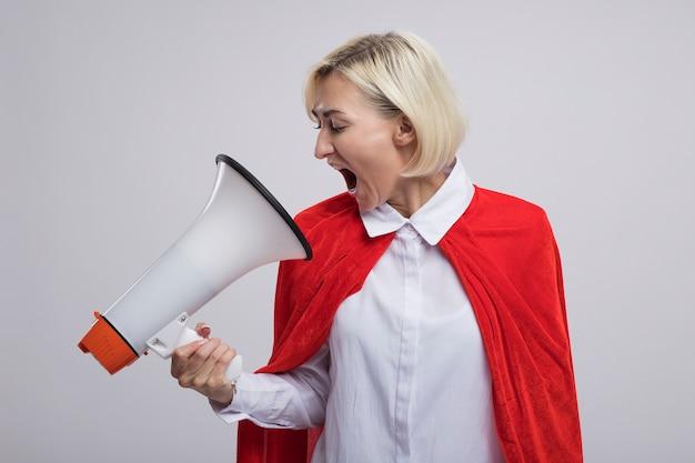 Blonde superheldin mittleren alters in rotem umhang, die lautsprecher hält und anschaut und schreit