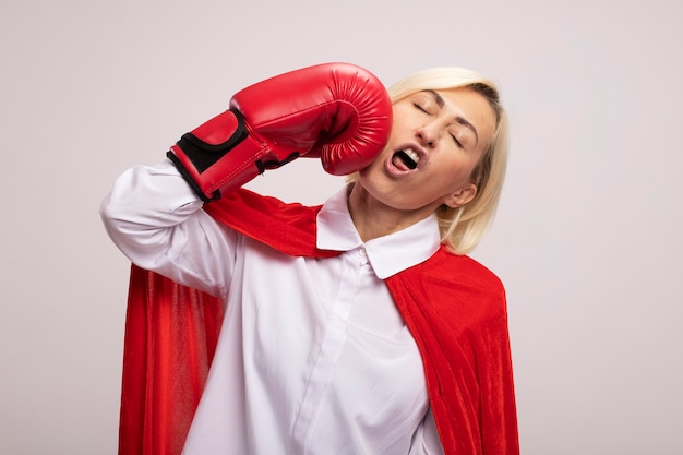 Blonde superheldin mittleren alters in rotem umhang mit boxhandschuhen, die sich mit geschlossenen augen ins gesicht schlägt