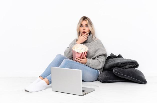 Blonde teenagerfrau, die popcorn isst, während sie einen film auf dem laptop sieht, überrascht und schockiert, während sie richtig schaut