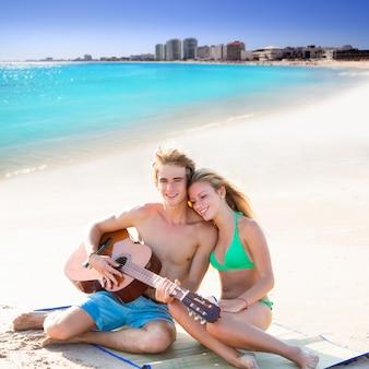 Blonde touristische paare, die gitarre am strand spielen