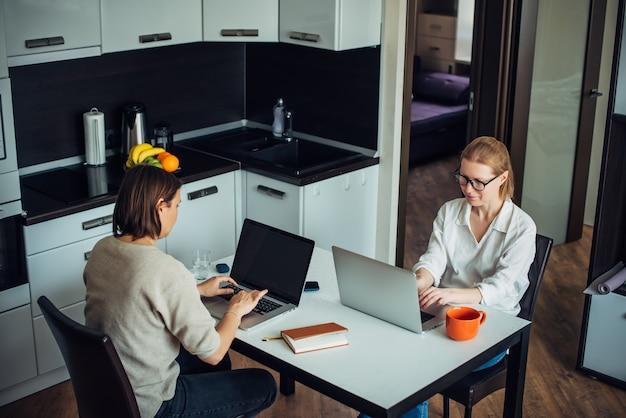 Blonde und brünette arbeiten an laptops und sitzen sich an einem tisch in der küche gegenüber. coworking in gemütlicher wohnlandschaft.