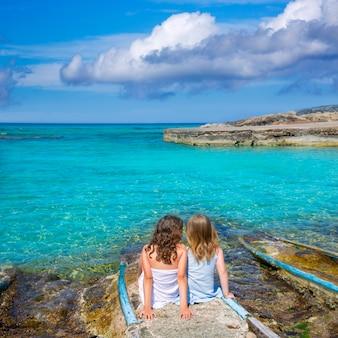 Blonde und brünette kindermädchen, die auf strandhafen sitzen