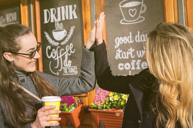 Blonde und brunettefrauen, die kaffee trinken und hände rütteln