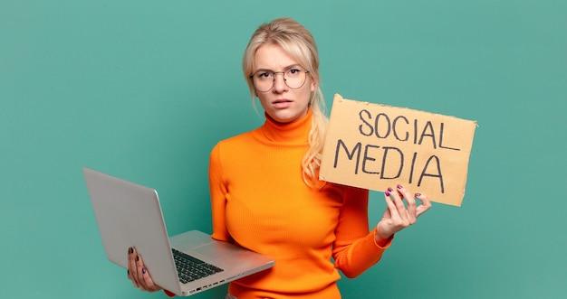 Blonde vorfrau mit laptop, social-media-konzept