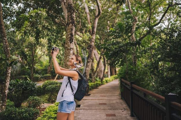 Blonde wandererfrau des reisenden, die fotos im tropischen wald machend, reiseabenteuer-natur in china, touristischer schöner bestimmungsort asien, sommerferien-urlaubsreise, kopienraum für fahne geht