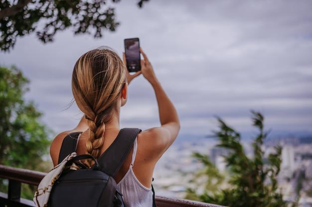 Blonde wandererfrau des reisenden, die fotos von der aussichtsplattform übersehend das stadtzentrum machend geht. reiseabenteuer in china, touristischer schöner bestimmungsort asien, sommerferien-urlaubsreise