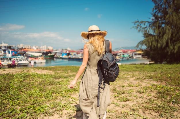 Blonde wandererfrau des reisenden in der hinteren ansicht des strohhutes geht entlang die küste an den fischerbooten des piers. reiseabenteuer in china tropischer insel asien-tourist. sommerferien-ferienreisekonzept