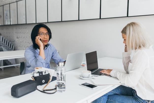 Blonde webentwicklerin, die auf tastatur tippt und vor asiatischem studenten in gläsern sitzt