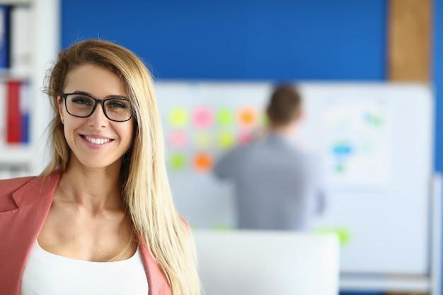Blonde weibliche angestellte, die im büro lächelt