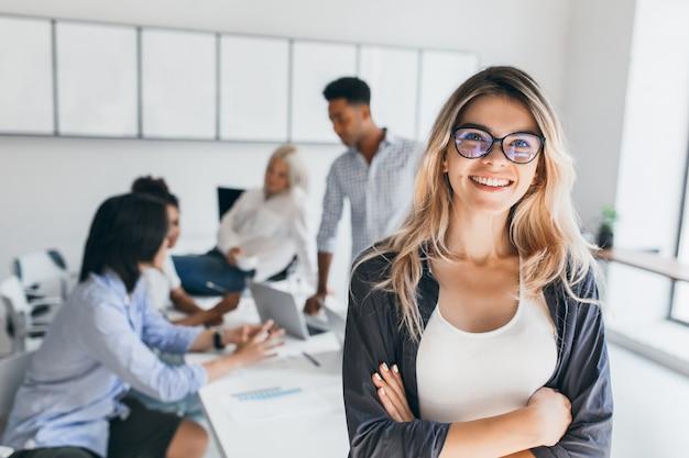 Blonde weibliche führungskraft, die mit lächeln und verschränkten armen während des brainstormings mit managern aufwirft. innenporträt des europäischen studenten, der zeit in halle mit asiatischen und afrikanischen freunden verbringt.