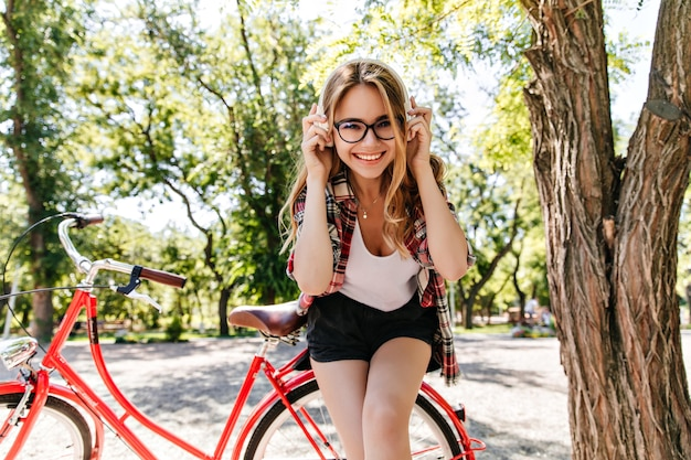 Blonde wundervolle frau, die musik im schönen park hört. erfreutes kaukasisches mädchen in den kopfhörern, die mit lächeln neben fahrrad aufwerfen.