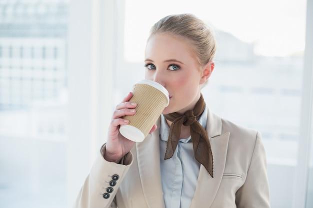Blonde zufriedene geschäftsfrau, die aus wegwerfschale heraus trinkt