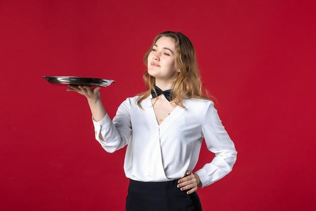 Blonde zufriedene weibliche serverschmetterling am hals und hält tablett auf rotem hintergrund