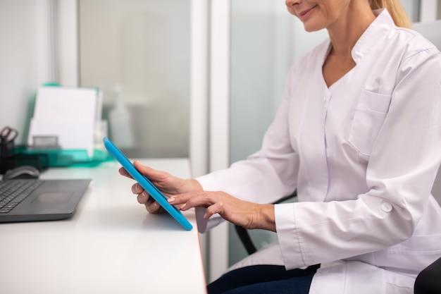 Blonder angenehmer arzt, der den bildschirm der tablette berührt, während er nach benötigten informationen sucht