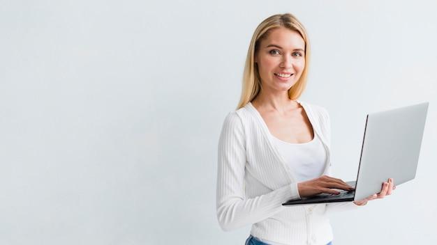 Blonder angestellter, der laptop auf weißem hintergrund hält