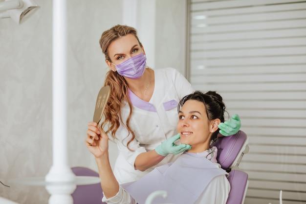 Blonder attraktiver zahnarztarzt in der medizinischen maske und in den handschuhen, die mit brunette weiblicher patientin darstellen, die den spiegel hält und lächelt.