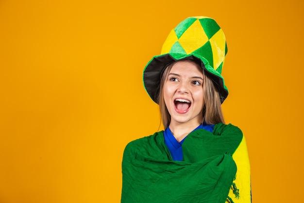 Blonder brasilianischer fan feiert auf gelbem hintergrund mit brasilianischer flagge