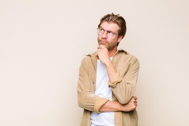 Blonder erwachsener kaukasischer mann, der denkt, sich zweifelhaft und verwirrt fühlt, mit verschiedenen optionen und sich fragt, welche entscheidung zu treffen ist