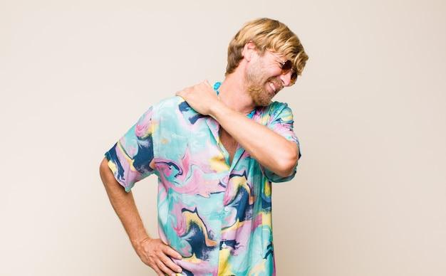 Blonder erwachsener kaukasischer mann, der sich müde, gestresst, ängstlich, frustriert und depressiv fühlt und unter rücken- oder nackenschmerzen leidet