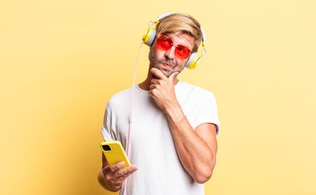 Blonder erwachsener mann denkt, fühlt sich zweifelnd und verwirrt mit kopfhörern