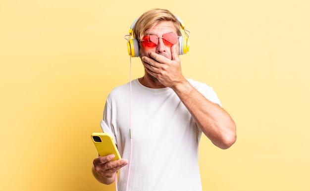 Blonder erwachsener mann, der den mund mit den händen bedeckt, mit einem schockierten kopfhörer