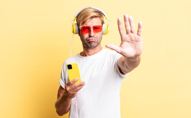 Blonder erwachsener mann, der ernst aussieht und offene handfläche zeigt, die eine stopp-geste mit kopfhörern macht
