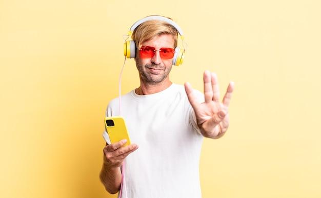 Blonder erwachsener mann, der freundlich lächelt und aussieht und nummer vier mit kopfhörern zeigt
