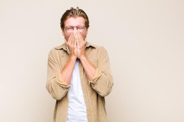 Blonder erwachsener mann, der glücklich, fröhlich, glücklich und überrascht sieht, mund mit beiden händen bedeckend