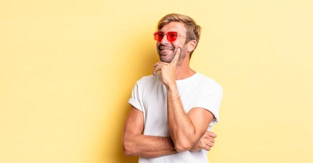 Blonder erwachsener mann, der glücklich lächelt und träumt oder zweifelt und eine sonnenbrille trägt
