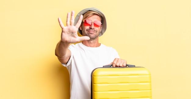 Blonder erwachsener mann, der lächelt und freundlich aussieht und nummer fünf zeigt. reisende-konzept