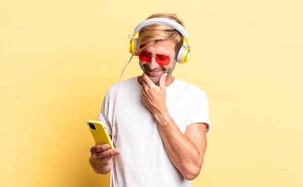 Blonder erwachsener mann, der mit einem glücklichen, selbstbewussten ausdruck mit der hand am kinn mit kopfhörern lächelt