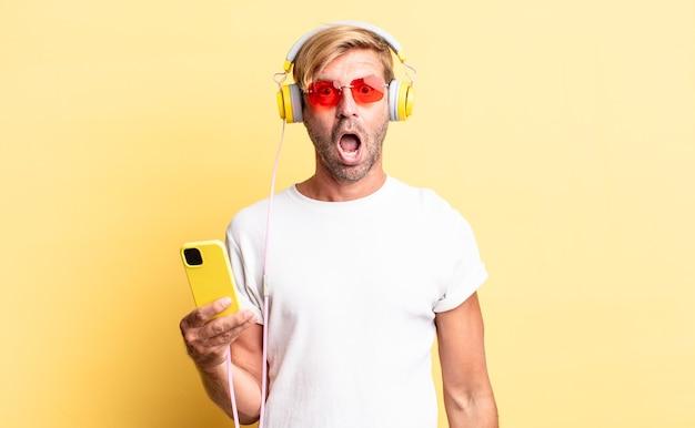 Blonder erwachsener mann, der mit kopfhörern sehr schockiert oder überrascht aussieht
