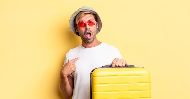 Blonder erwachsener mann, der schockiert und überrascht mit weit geöffnetem mund aussieht und auf sich selbst zeigt. reisende-konzept