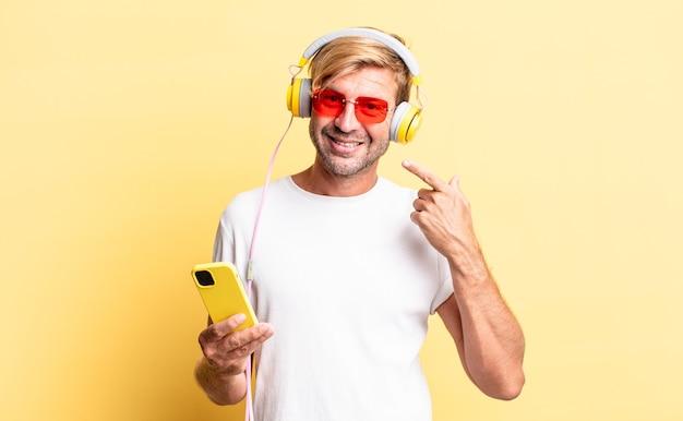 Blonder erwachsener mann, der selbstbewusst auf sein breites lächeln mit kopfhörern lächelt