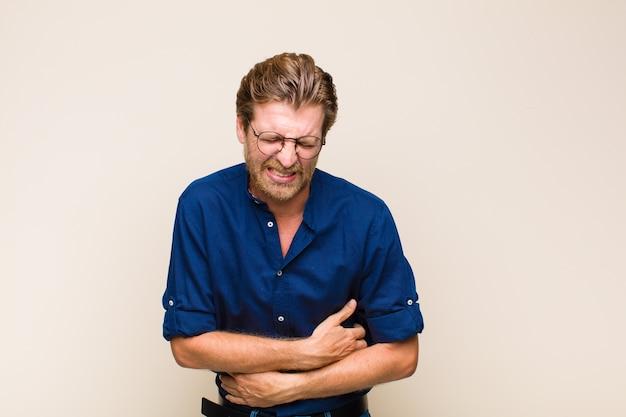 Blonder erwachsener mann, der sich ängstlich, krank, krank und unglücklich fühlt und unter schmerzhaften bauchschmerzen oder grippe leidet