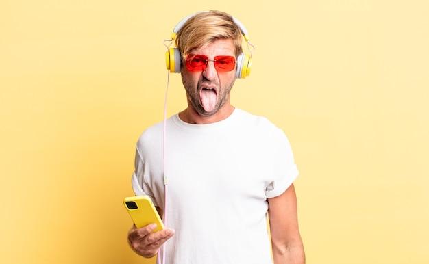 Blonder erwachsener mann, der sich angewidert und gereizt fühlt und mit kopfhörern die zunge herausstreckt